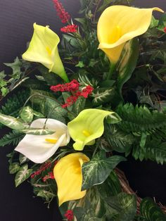 (Detail) Spring/Tropical Wall Piece: Yellow & Light Green Calla Lilies nested amongst tropical greens: Boston Fern, Hosta leaf, bush ivy, Star Ivy on a grapevine wreath. Original design and arrangement by http://nfmdesign.synthasite.com/