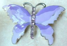 A pretty, large enamel and rhinestone detailed butterfly brooch. The brooch design is of a butterfly,  with wings in lovely enamel shades of lilac and purple. The central body of the butterfly is studded with lilac rhinestones