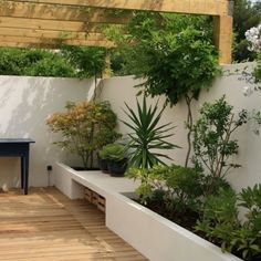 Un jardin sur une terrasse en bois et muret blanc