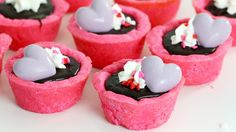Recipe with video instructions: Pink sugar cookie tart shells filled with strawberry dark chocolate ganache. Perfect for a special someone or a Galentine's Day party! Ingredients: Tart Shells:,  2 cups flour,  ¼ tsp salt,  ½ tsp baking powder,  ½ cup unsalted butter,  1 cup sugar,  1 egg,  2 tbsp milk, pink food colouring,  ½ tsp vanilla extract, Ganache Filling:, 8 oz strawberry-flavoured dark chocolate (I used Lindt Excellence), pinch of salt, ¾ cup whipping cream, hot, Melted white cho...
