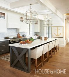 A vent hood adorned with wood panels is well-suited to this kitchen's laid-back aesthetic, and is a fitting choice given the cottage's lakeside location in Muskoka, Ontario. | Photographer: Virginia Macdonald | Designer: Cory deFrancisco