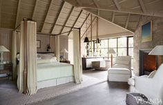 """""""The bed is snug and inviting in this very tall room,"""" says Saladino. """"The mosquito netting isn't really necessary, but I love the fact that it provides them with a little protected space to hide in at night."""" <br /><br />Enormous bronze doors lead to a balcony overlooking a forest of birch, maples, and ferns, giving the bedroom the feel of a tree house.<br /><br /><em><strong>The open plan of the master bedroom and bath gives the space an airy, loftlike feel. Bed, Holly Hunt Studio. Linens…"""