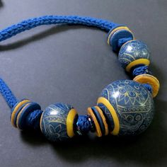 Hollow bead necklace, denim by Pavla Cepelikova (polymer clay) - I'd love to know how the designs on the large beads are created.