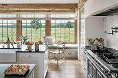 Large kitchen windows provide a view of surrounding farmland at a family's barn-style house on Marth... - Photo: Nikolas Koenig