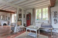 La pièce à vivre de la maison d'hôtes L'Épicerie du Pape avec ses colombages évidés et repeints en blanc et son sol recouvert d'anciennes tomettes en terre cuite