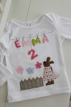 Liebevoll und sehr aufwändig gestaltetes Langarmshirt aus reiner Baumwolle in weiß. Süßer Hase aus Bio- Westfalenplüsch in braun mit einem gepunkteten Kleid, einem Gartenzaun und süßen Blümchen....