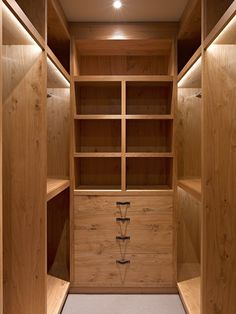 Pippy oak walk-in wardrobe with bespoke leather drawer handles lit beautifully by concealed LEDs