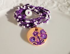 Crochet and clay boho necklace, purple, white beaded crochet necklace, clay flowers stamped pendant, hand painted by dzinebug on Etsy