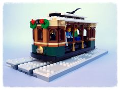 I was motivated to design and build this Winter Village Tram once it became apparent that this year's Winter Village set is a re-release of the first one. I always felt the Winter Village needed some public transportation, and I think a tram fits the bill. I opted for an open design for a more fun and easy minifigure display/access. The tram is inspired by older era electric trams that were adorned with wood trims and detailing, which seems to be the official Winter Village set's time… Lego Winter Village, Lego Village, Lego Halloween, Halloween Village, Lego Calendar, Lego Minion, Lego Christmas, Lego Trains, Lego Blocks