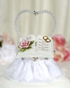 $26.95 This lovely cake top showcases a faux pearl heart and a beautiful fine porcelain bible with a beautiful pink rose in bloom and a pair of entwined wedding rings accented with 24K gold. Skirt is made of organza. The inscription from 1 Cor. 13.7 reads: <br />Love... <br />Bears all things <br />Believes all things <br />Hopes all things <br />End...