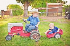 So cute older brother pull n his younger brother in the mini tractor and wagon