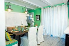 Slipcovered chairs and a built-in bench with striped upholstery cushions surround a wooden table in this update take on a Southern cottage. Pistachio green walls, nautical sconces, pale wood floors and billowing white drapes complete this mod-cozy look. The made over dining space was featured on HGTV's series Renovation Raiders.