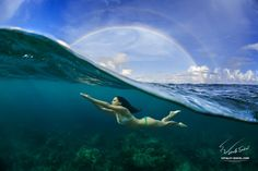 © 2015 Vitaliy Sokol Big picture I sell here:Underwater Sport Postcard. A freediver floating under water surface in ocean. A rainbow appear on cloudy sky over beautiful seascape Maldives, May-june 2015, home reef, rainbow and girl freediver  Thx for watching