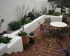 petit jardin méditerranéen terrasse andalouse style espagne mur blanc chaux chaises vintage fer plantes méditerranéennes jolies fleurs méditerranée