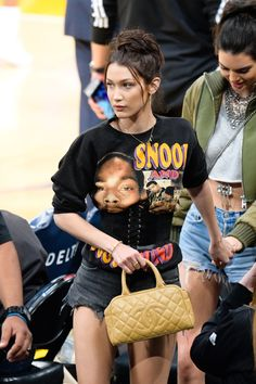 On Tuesday night, Kendall Jenner and Bella Hadid went for a casual girls' night and hit up the Staples Center in Los Angeles to watch a Laker game.  Hadid didn't stray far from her sultry-meets-sporty style. She wore a Snoop Dogg sweatshirt with a corset surprisingly layered on top, black cut-off shorts, a beige Chanel handbag and black Louboutin pumps.