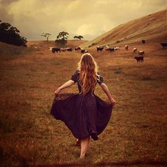 it almost looks like she's curtseying to those distant cows...