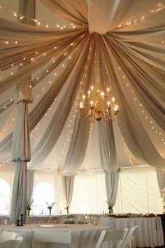 The addition of twinkle lights and a chandelier to the draped fabric really transform this space into something special