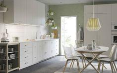 ホワイトの大きなキッチンにホワイトのワークトップ、取っ手、ノブ。バーチのオープン収納とホワイトのオーブンと電子レンジ。