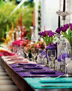 Colorful table setting for wedding decor: purple, orange, yellow, pink.