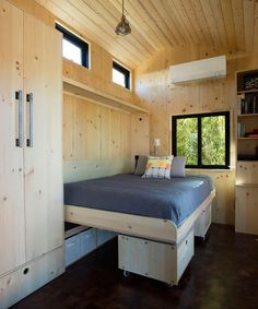 In the main living area is a Kimberly gasifier wood stove, queen size wall bed, modular seating cubes with built-in storage, and built-in closet, shelves, and desk. #smallroomdesigntinyhouses