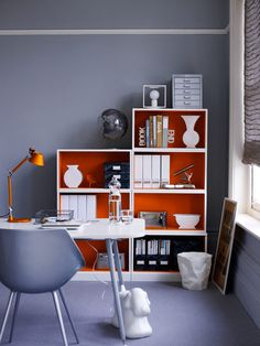 Painting the interiors of shelves a bright orange highlights the shapes of white ceramics and storage containers.