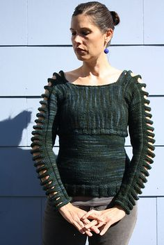 A pullover that is knit from cuff to cuff with horizontal slits and a square neckline which is then picked up below bust and knit down.