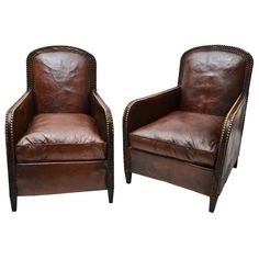 1920's club chairs, original leather and brass studs, loose seat and tapered legs. France