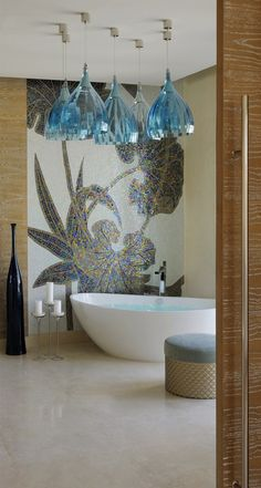 Beautifully unique lighting fixtures accent the gorgeous tile mosaic wall of this bathroom.
