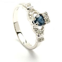 This stunning gem set Claddagh ring features twelve sparkling diamonds surrounding an unusual heart shaped sapphire center stone of 0.45 carats. The ring is handcrafted from 14k white gold and would be the perfect choice for an engagement ring.  Also available is a matching wedding band which fits perfectly against the Claddagh ring and is enhanced with accent diamonds.  Width: 2.5mm Weight: 2.6g  Stone: Sapphire Stone Shape: Heart Stone Dimensions: 5x5mm Stone Weight: 0.45  Diamond Carat…