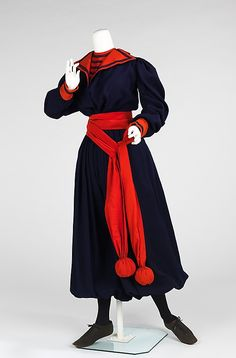 Navy wool gym suit with red cotton collar, cuffs, and sash, American, 1893-98. This ensemble is a typical garment for women participating in a physical education course in the late 19th century. The middy style blouse and bloomers allowed movement and fully concealed the female figure, while the balls on the end of the sash could be used as props in calisthenics. Worn with flat leather oxfords.