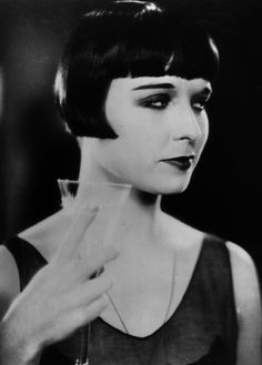 Louise Brooks with drink.  Champagne, of course!
