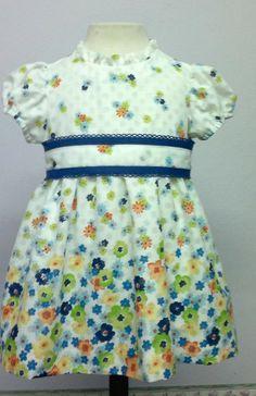 Vestido para bebe niña estampado de flores combinado con fajín con puntillas azulinas. Falda con combinación interior.