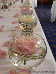 Wedding flowers – mini fishbowls and tealights line the front of the long top table for the wedding breakfast with a scattering of rose petals – by Floral Accents
