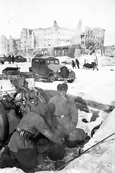 "A little-known photograph by the famous Soviet photographer Natalia Bode, on the streets of liberated Stalingrad. Winter 1943. Two Russian soldiers from the team of 76-mm regimental gun mod. 1927 cooking dinner from captured products taken from dead soldiers Wehrmacht. At one Russian soldier wearing German's lap belt with the inscription ""Gott mit uns"" (""God with us""). In the background are two light tank T-70."