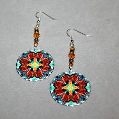 Silver dangle earrings with a Monarch butterfly mandala sacred geometry charm titled Timeless Treasure. <br /> <br />These lightweight, dainty silver earrings begin with a dangle of chocolate and light brown glass beads and amber Swarovski crystals that accentuate the colors in the mandala charm that has scalloped edges that catch the light. The mandala charm is 1 ...