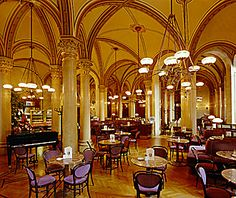 Cafe Central, Vienna, Austria. Famous coffeehouse in Vienna opened in 1876, and in late 19th century became key meeting place of the Viennese intellectual scene. Today a tourist spot and popular café marked by its place in literary history. First coffeehouse in Austria opened in Vienna in 1683, by using supplies from the spoils obtained after defeating the Turks. Melange is Viennese coffee, which comes mixed with hot foamed milk and a glass of water.