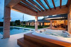 A banheira de hidromassagem Jacuzzi fica em um bloco separado, sob o pergolado fechado com vidro, e de frente para piscina com revestimento em pastilhas 4 cm x 4 cm Jatobá. O projeto arquitetônico da casa no interior paulista é de Maurício Karam