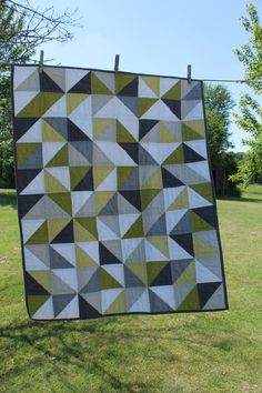 Quilt is constructed of Kona cotton solids in a range of green, greys and white. The squares are randomly placed for an interesting, if not,