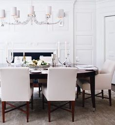 Beautiful all white dining room with a contrasting espresso color dining table, which adds a bit of richness to the monochromatic color scheme.  The elegant large chandalier with white lamp shades is a chic touch.