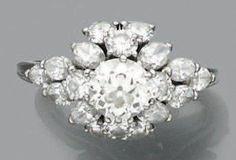 Bague en platine ornée d'un diamant de taille ancienne dans un bel entourage de diamants de taille brillant et de navettes. Poids du diamant central: env 1.25 carats Tour de doigt: 56 Poids brut: 8.5… - Aguttes - 09/10/2014