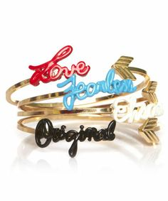 The Motto Bangle Set: Love, Fearless, Original, and Ehsani color text finishes each of four gold plated bangle bracelets with logo detail. Adjustable. Sold as a set but can also be worn separately. Great for stacking!