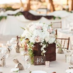 """@unveiledhawaii back again! """"White linens, light florals and a wooden centerpiece stand make for one elegant table setting! 