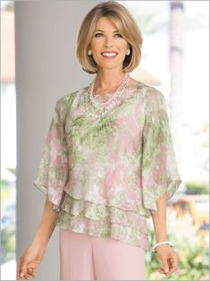 The ultimate in formal flattery. This rare and refi ned top creates a slender silhouette with a triple-tiered hem that is cut at an angle. Designed in an airy chiffon. Floral print is romanced in a palette of pastels Blouse Styles, Blouse Designs, Wedding Pantsuit, Clothes For Women Over 50, Tiered Tops, Alex Evenings, Evening Tops, Beautiful Blouses, Short Tops
