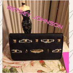 """NWT-BETSEY JOHNSON BLACK SIGNATURE WALLET FUN & PRACTICAL! BLACK LEATHER WITH WHITE BETSEY JOHNSON LOGOS AND GOLD-TONE TAG AND DECORATIVE STUDS/ZIPPER WALLET. LARGE! 4.5"""" HIGH BY 8"""" LONG And 1"""" DEPTH EMPTY. GOLD-TONE METALLIC INTERIOR WITH SEVERAL CREDIT CARD HOLDERS. CENTER BLACK / PINK FLORAL ZIPPER COIN AREA. GREAT CHRISTMAS GIFT! Betsey Johnson Bags Wallets"""