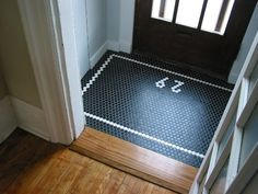Another black penny tile entryway with white border