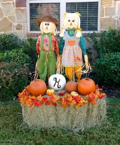 "Stacy's 2015 Fall yard decorations. I used a boy and girl scarecrow, a square bale of hay, several plastic pumpkins from craft store, and 2 fall leaf strands. I spray painted one antique white and stenciled an ""H"" on it. I used glow in the dark spray paint on the med orange pumpkin. I love how it turned out!"