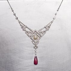 joganibhOld cut diamonds. A gorgeous pearl. A drop Burma no heat ruby. All set in a piece that melds elements of nature with geometric patterns. We love everything about this Edwardian necklace.