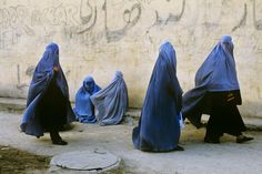 Women wearing full Burqas. In Afghanistan, most women wear these so men will not look at them. This is especially common among married women, as their husbands do not want them being looked at.