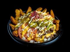 Grilled cheese burger Fudd's burger fry stak, NRG Stadium (Houston Texans)  Thick cut French fries topped with crumbled hamburger, crispy bacon, hot cheese sauce and traditional burger fixings.