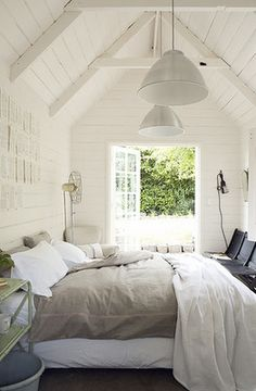 I love the high ceilings, the painted boards, the big glass door leading outside, and that soft, cushy-looking bed that makes me first want to jump on it, then curl up for a nap.